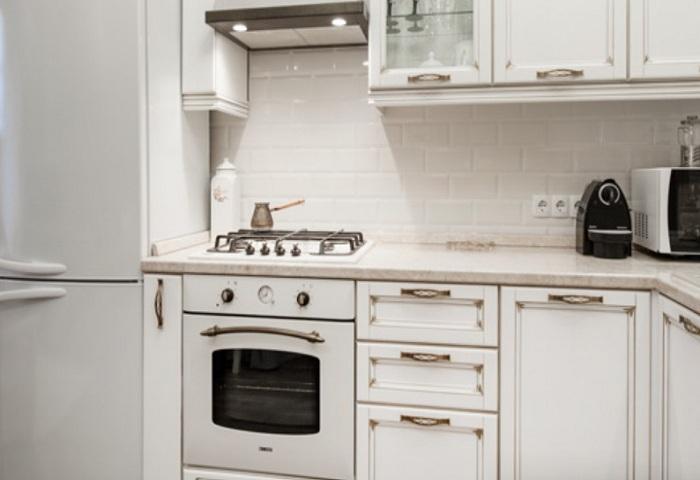 Белая кухня с золотой патиной.